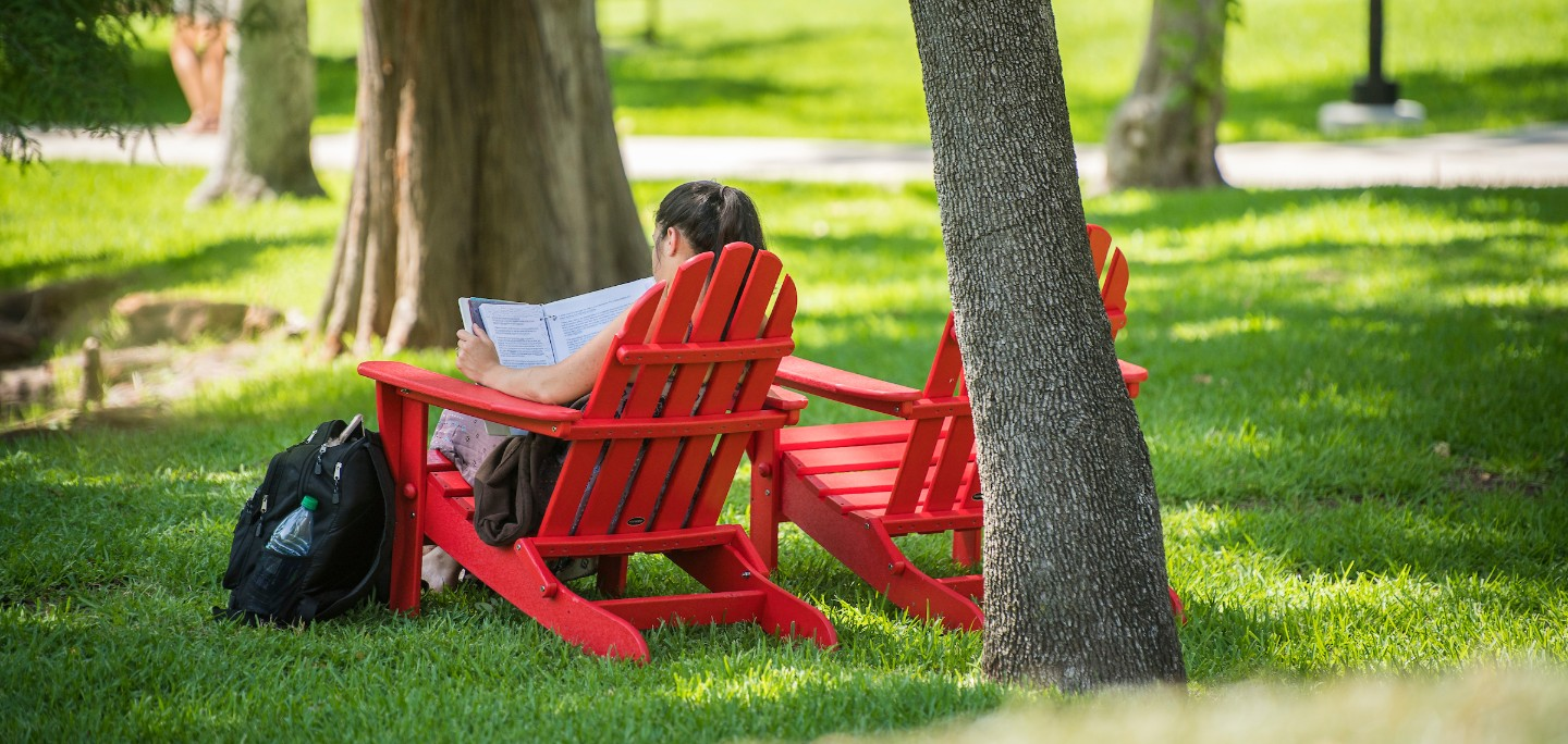 Girl relaxing in red chair under trees