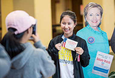 Student taking a photo next to a life-size cutout of Hillary Clinton