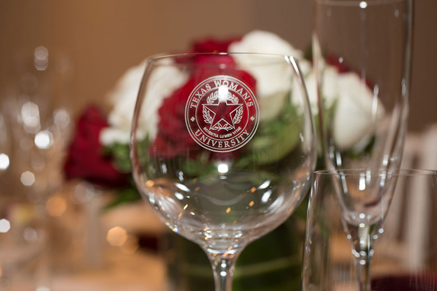 a close-up of a TWU wine glass with the university seal etched on it