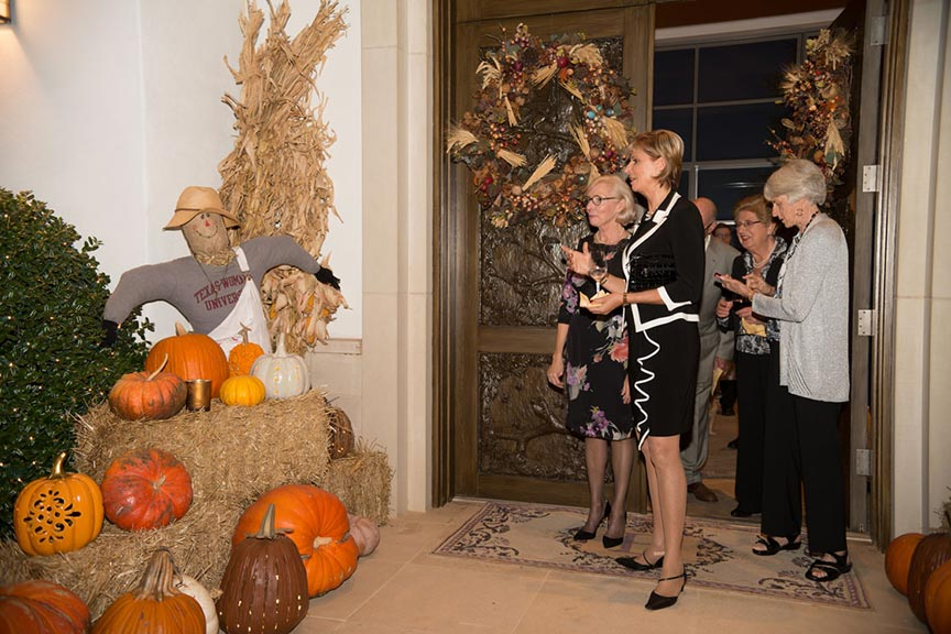 Chancellor Feyten admires an autumn display of a scarecrow and pumpkins