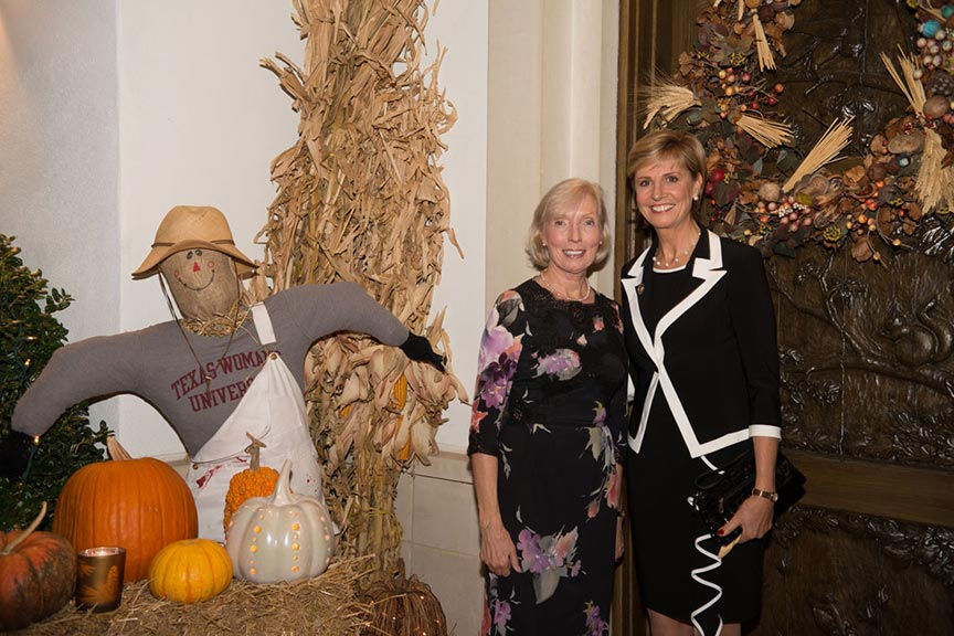 Chancellor Feyten has her photo taken with Sue Bancroft by the autumn display scarecrow