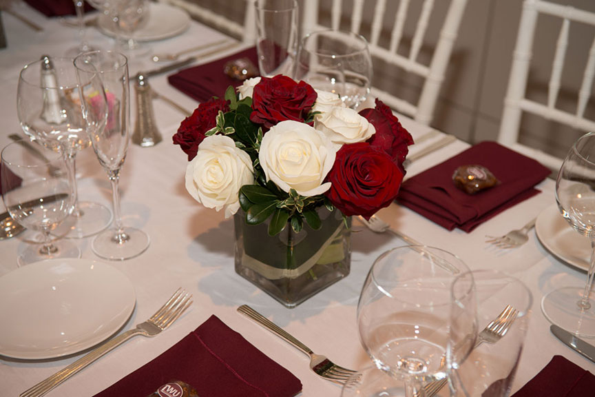 a vase with a group of red and white roses on a dinner table