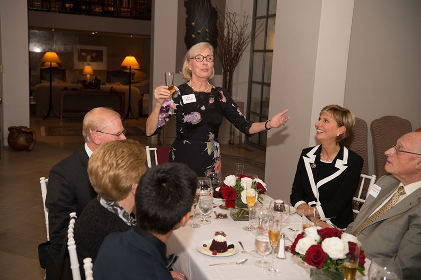 Sue Bancroft stands and proposes a toast at a dinner table with Chancellor Feyten