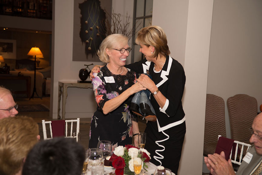 Chancellor Feyten embracing Sue Bancroft at the banquet table