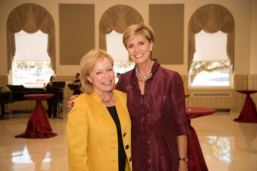 Chancellor Feyten and a woman in a yellow jacket smile together for a photo