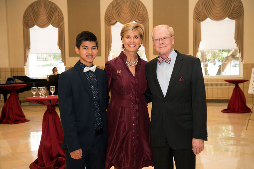 Chancellor Feyten and her husband Chad Wick pose together with a young man