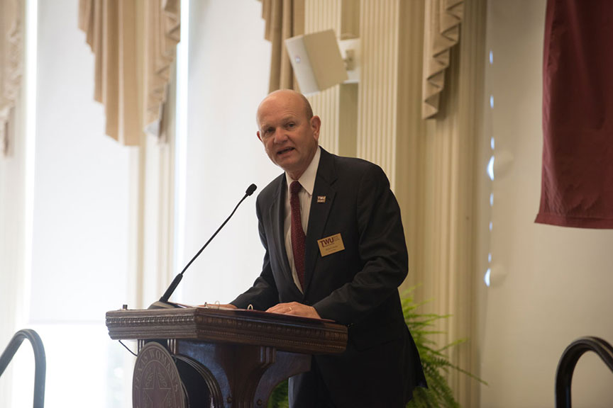Dr. Bob Neely speaks at a podium and microphone