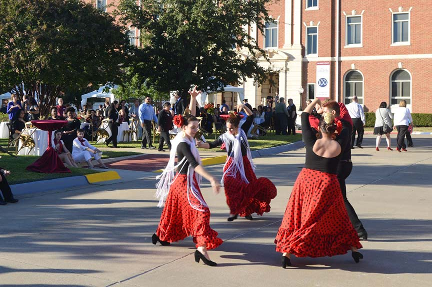 three young women dressed as flamenco dancers dance on the Pioneer Circle while a group of spectators look on from the lawn