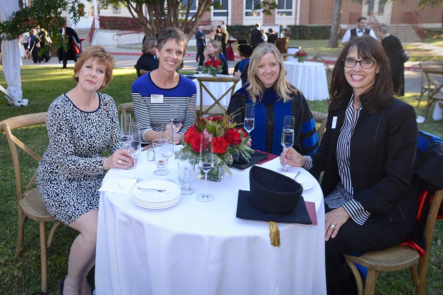 Four women sit at an outdoor table with a vase of red roses in the center