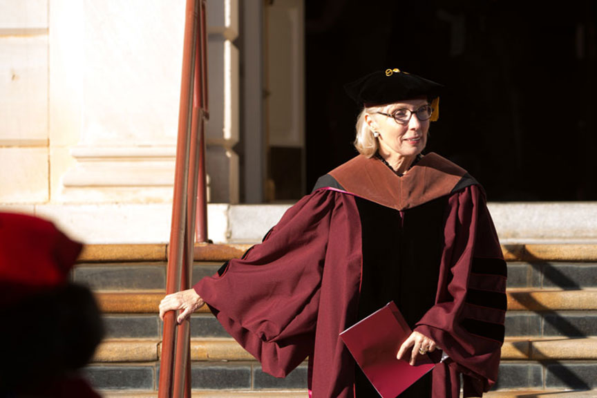 a woman in university regalia descends the steps of the Music building on Pioneer Circle