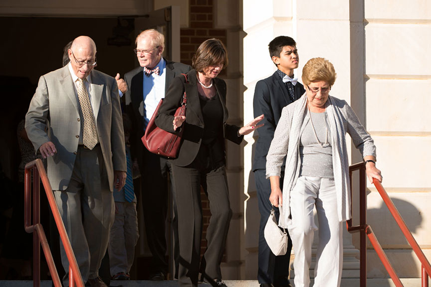 Chancellor Feyten's husband Chad Wick descends the steps of the Music building with a group of people