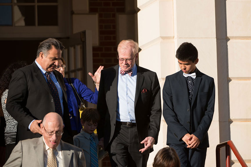 Chancellor Feyten's husband Chad Wick descends the stairs of the Music building with a young man beside him