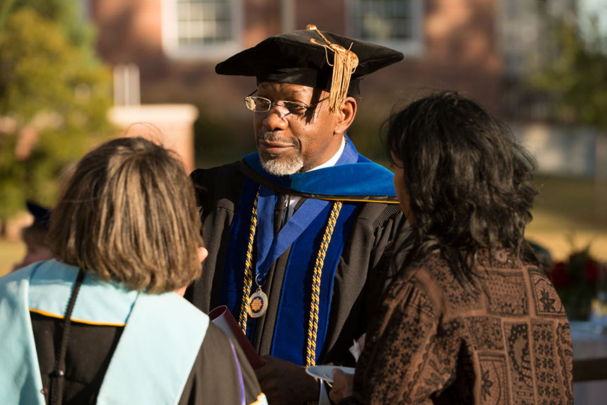a black man in university regalia speaks with two women, one also in university regalia