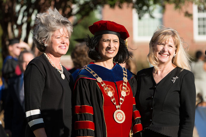 University of Houston Chancellor Renu Khator stands with two women on Pioneer Circle