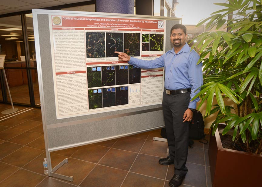 a man smiles and points to a scientific presentation poster
