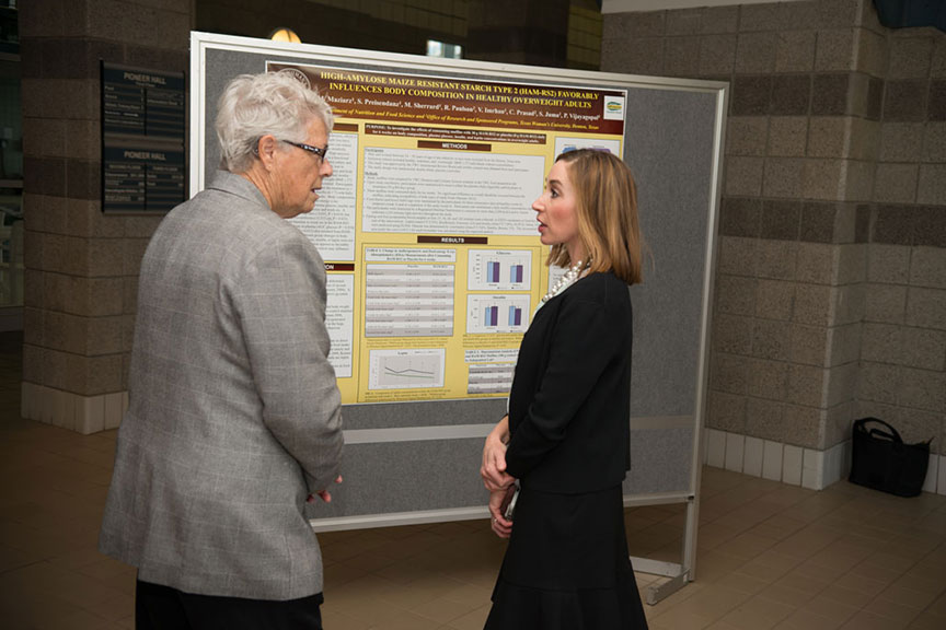 a man and woman stand and discuss a scientific presentation poster