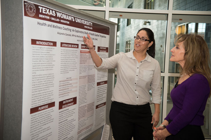 A woman explains her scientific presentation poster to an onlooker