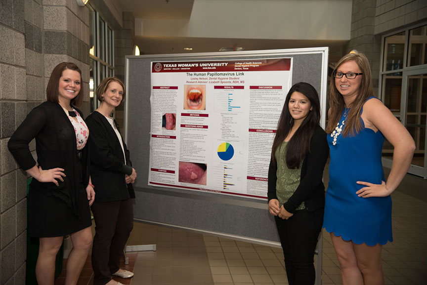 four women pose in front of a scientific presentation poster