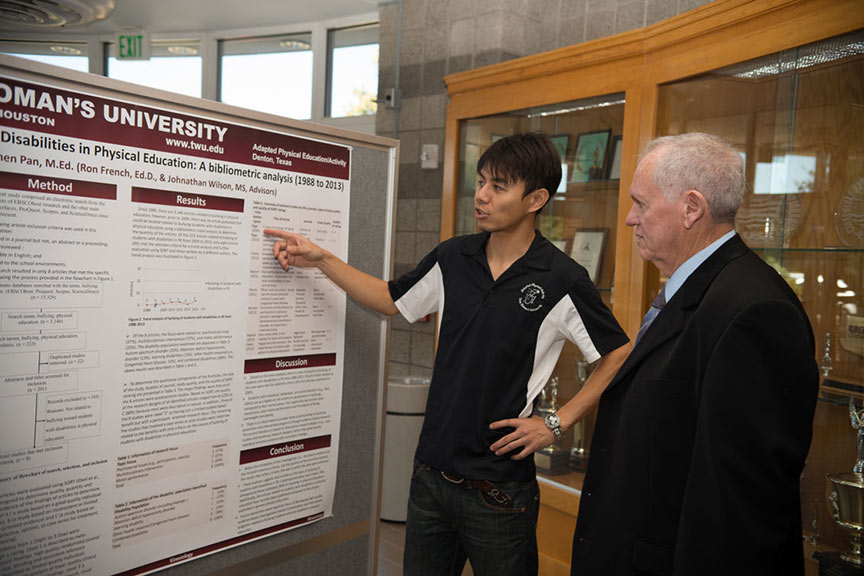 a young man explains his presentation poster to an onlooker