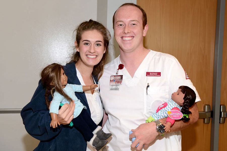 Two nursing students pose together with dolls for pediatric patients