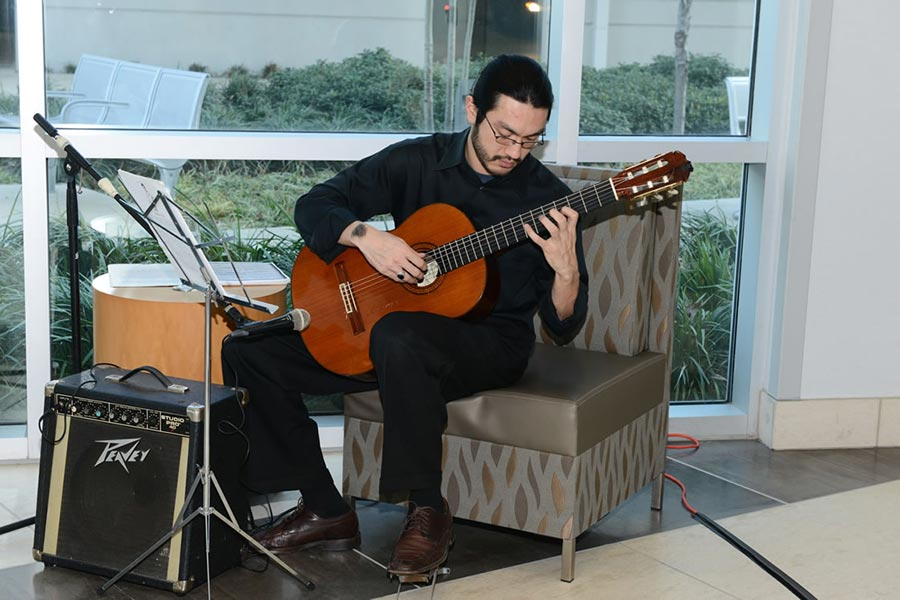 A seated dark-haired man plays guitar