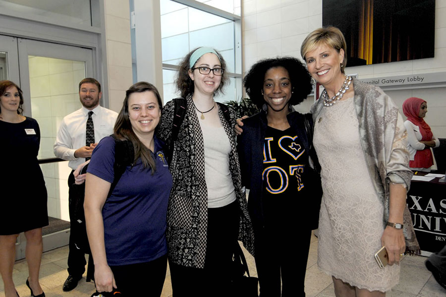 Chancellor Feyten poses with three students