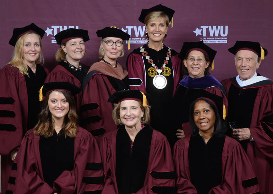 Chancellor Feyten in a group photo behind a TWU maroon backdrop