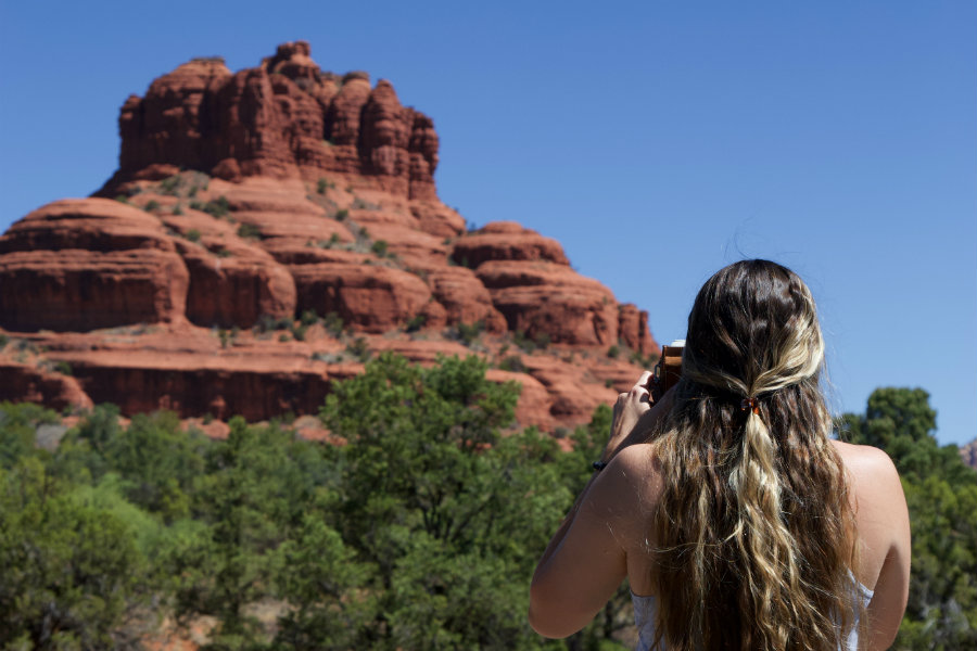 Angel Trosper standing in front of Bell Rock and taking a photo of the rock formation.