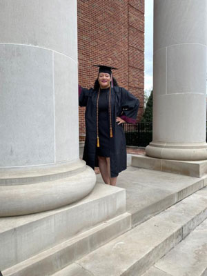 Cheryl Brown leans against the a library column on TWU's Denton campus in her graduation gown.