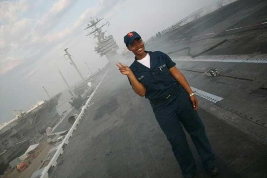 Chanel VanHook in her Navy military uniform on a foggy day with a Navy ship in the background.