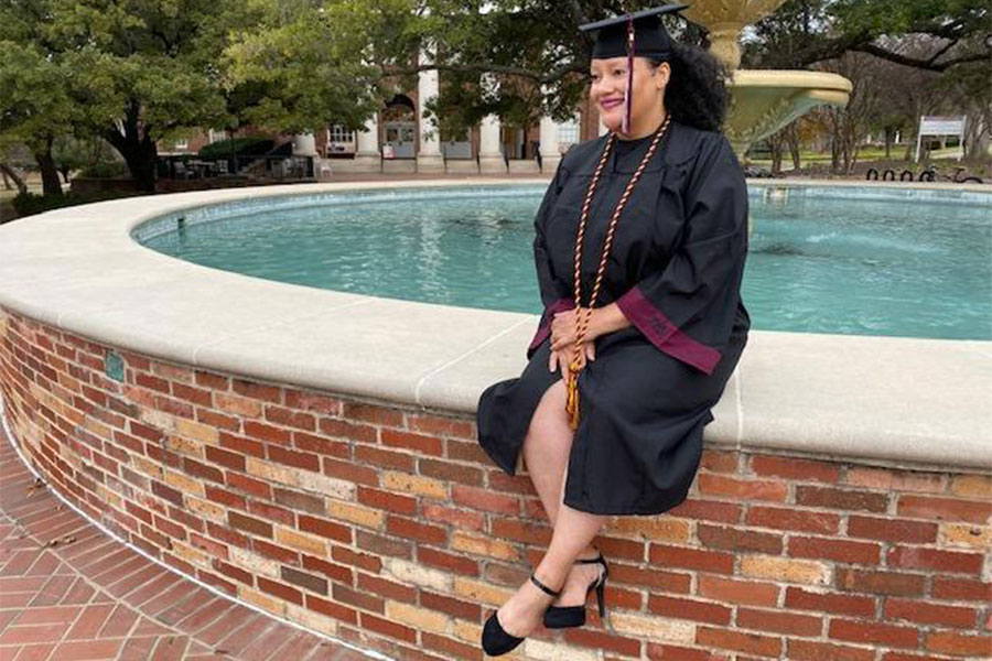Cheryl Brown sits by the fountain on TWU's Denton campus in her graduation gown.