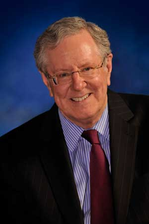 A headshot of Steve Forbes in a suit with a blue background.