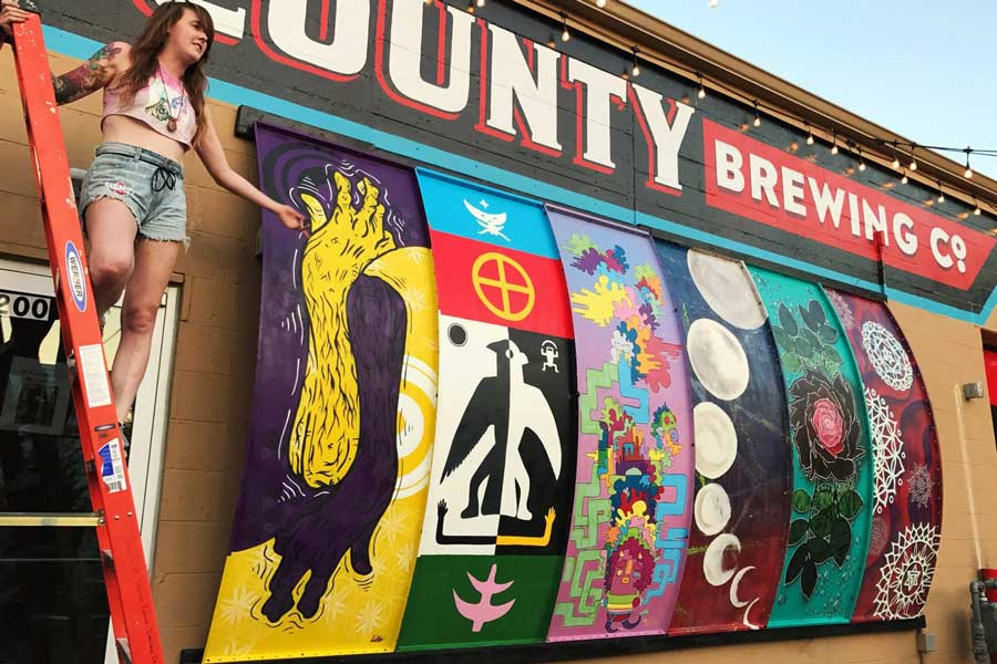 Katie Mont poses with a mural she painted outside Denton County Brewing Company.