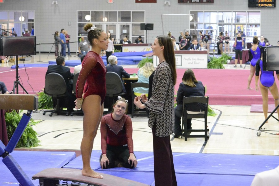 Lisa Bowerman coaching a gymnast before her routine in a gym setting.