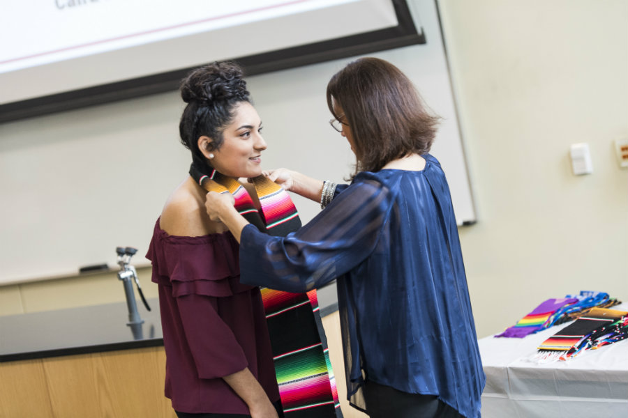 Becky Rodriguez placing a Raza Stole around the neck of a TWU student she mentored at the Multicultural Graduation event.