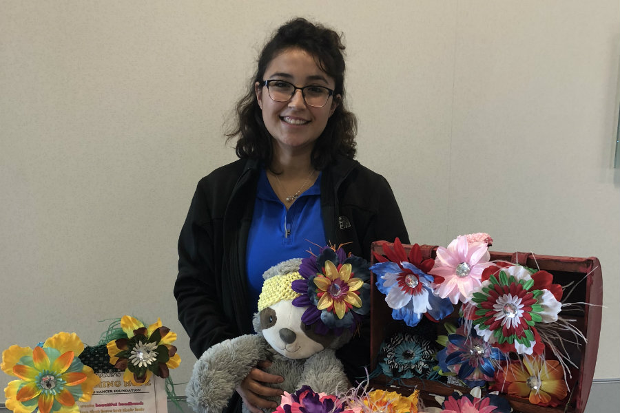 Meagan Ortega smiling in front of a table of crafts for Brooke's Blossoms.