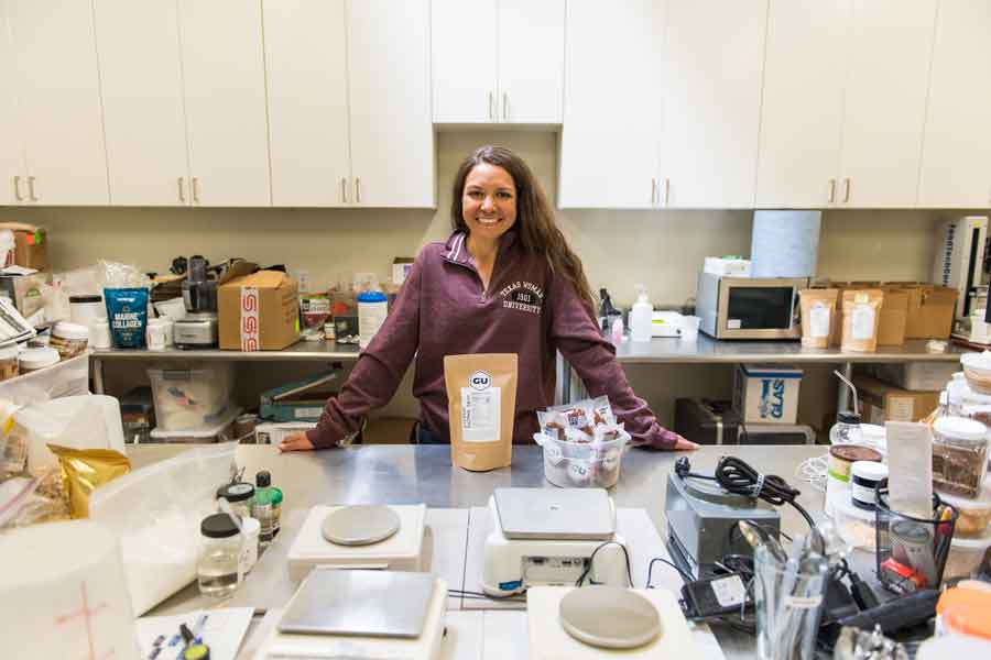 Roxanne Vogel in a GU Energy lab and surrounded by products.