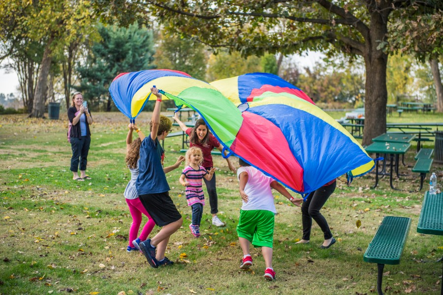 A TWU student playing with a group of young kids under a parachute at the Dallas Arboretum.