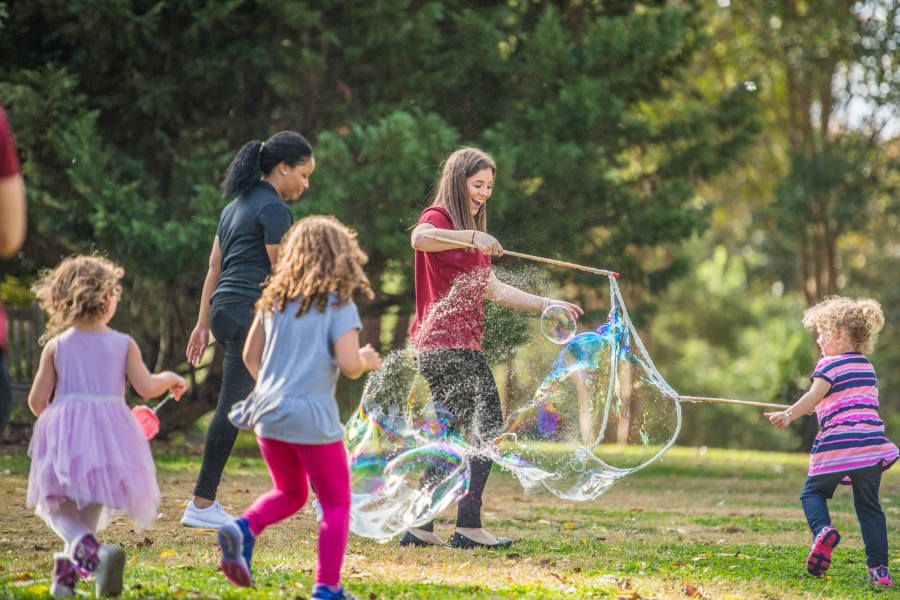 A TWU student playing with a bubble machine with young kids at the Dallas Arboretum.