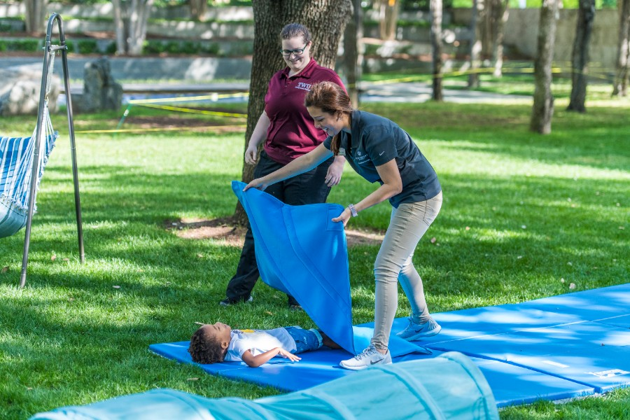 Two TWU students place a weighted blanket on a young child at the Nasher Sculpture Museum.