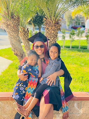 Kwashae Ruffin in a graduation cap and gown smiles with her two children
