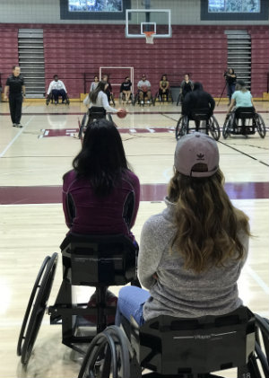 Women in wheelchairs play basketball