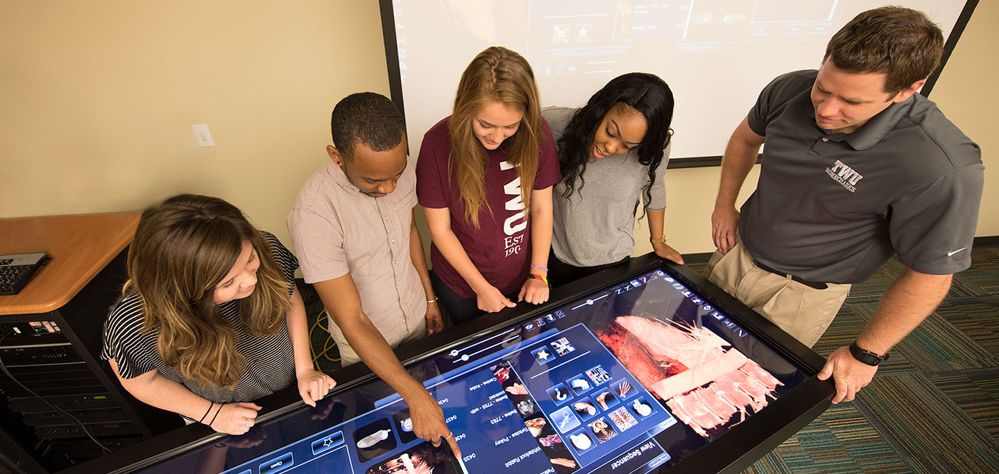 Kinesiology students learn about the effects of exercise and fitness on human anatomy with an anatomage table