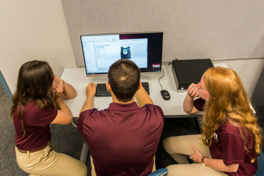 Three TWU students look at a 3D model on a computer screen