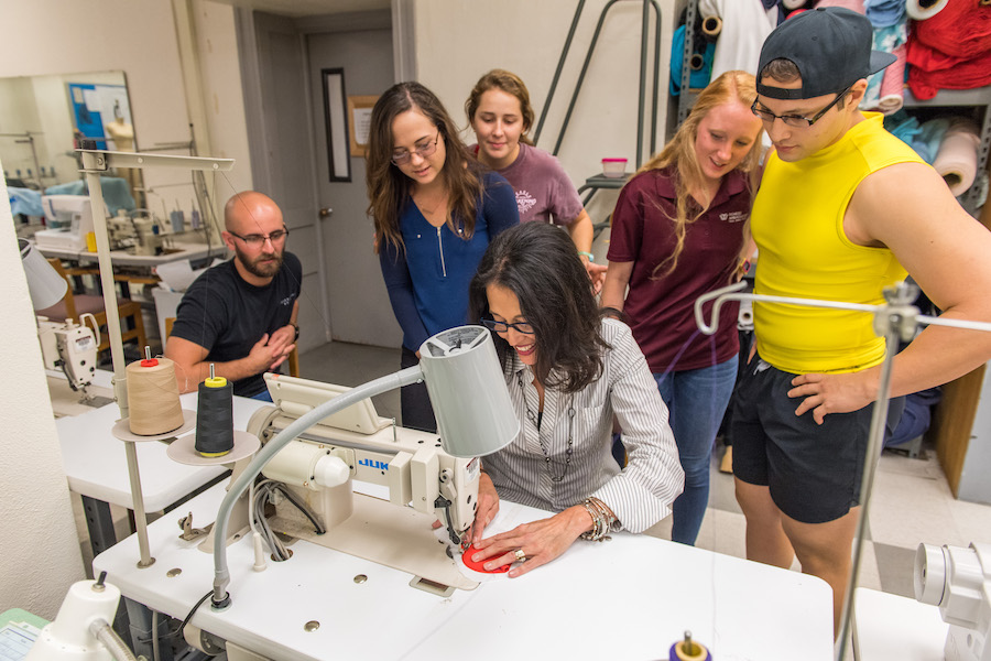 Five TWU students watch as Dr. Dragoo sews the prototype.