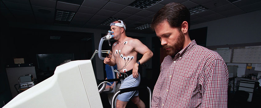 Student jogging on treadmill while professor reads data screen.