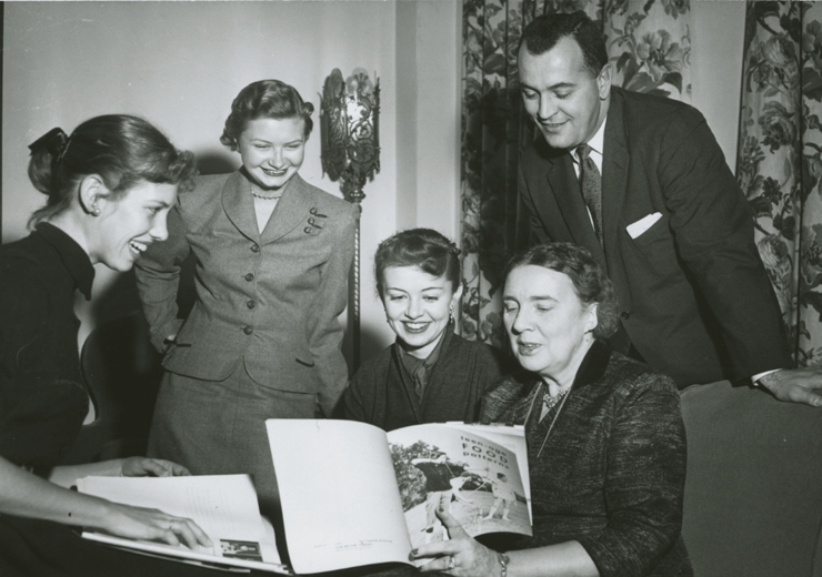 Dr. Pauline Beery Mack seated with a group of people, reading Teen-age Food Patterns.