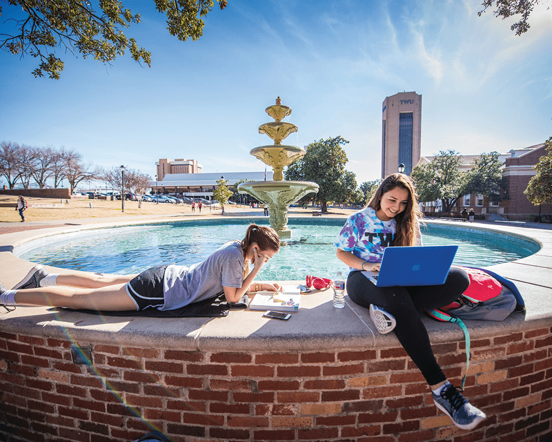 Two students sitting beside a fountain