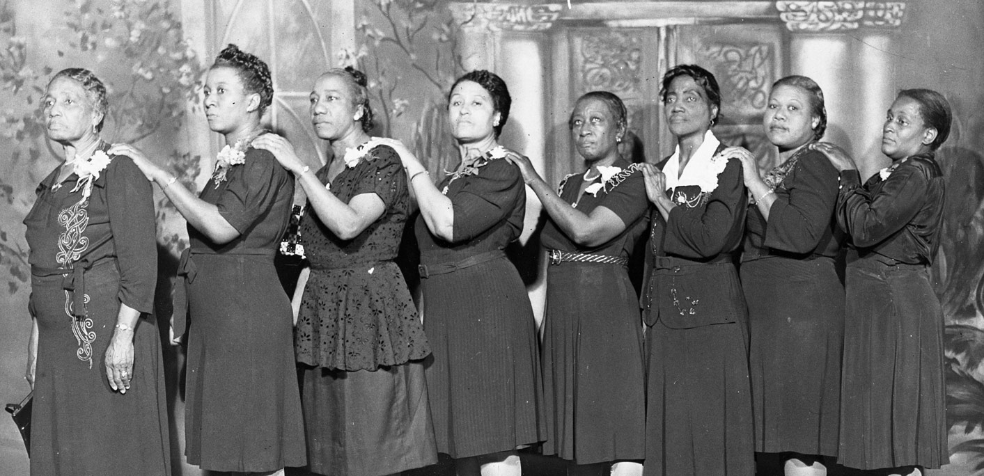 Eight of the maids and matrons of the Marlin Club all dressed in semi-formal dark dresses in front of a painted backdrop. L to R: Lucy Warren, A.W. Carroll, Madeline Williams, A.E.S. Johnson, Susie Ballinger, Lula Covington, Pearlie B. Matthews, unknown.