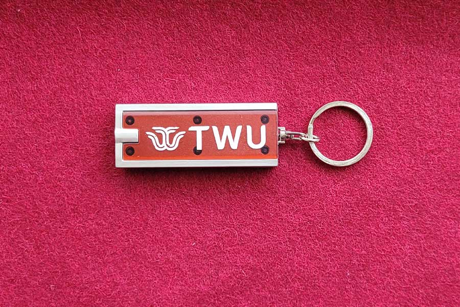 Flashlight keychain with TWU logo on it